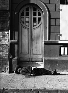 Homeless man laying by a door